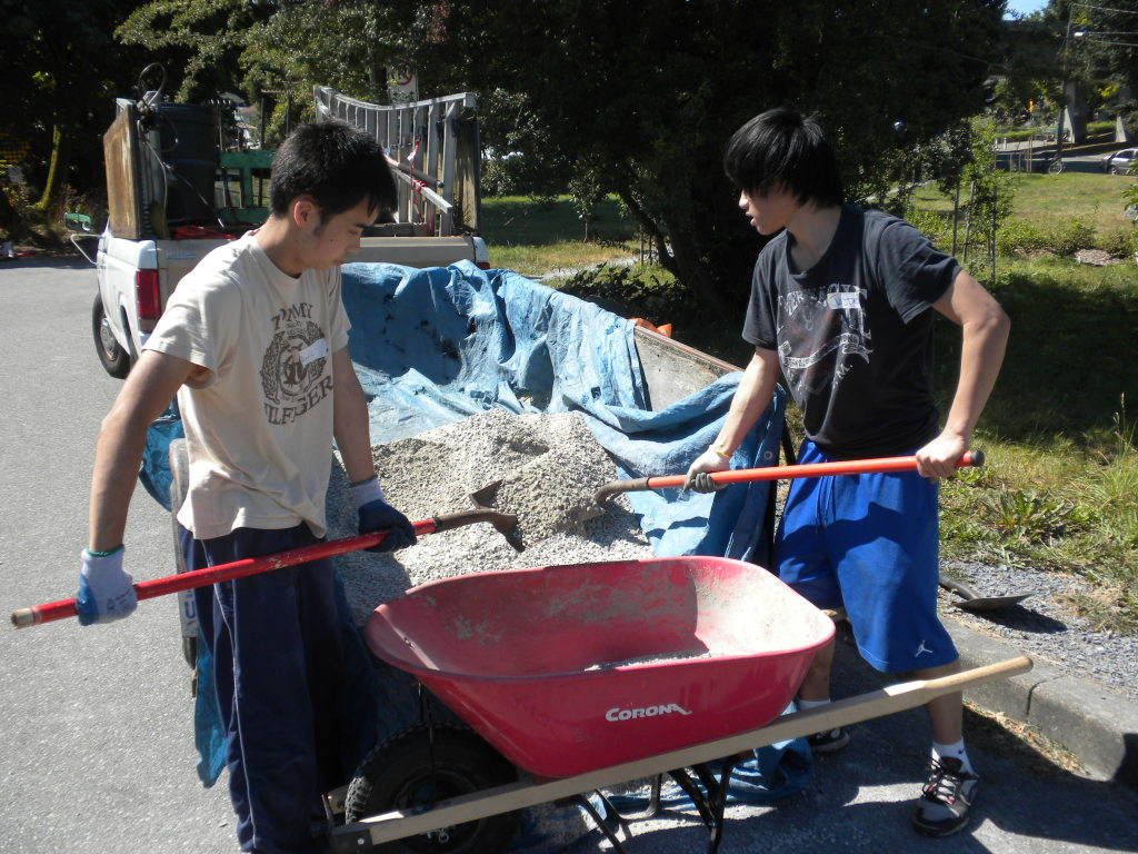 Shovelling gravel to prepare the base for the benches